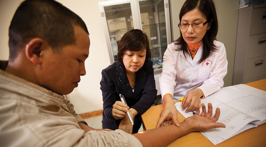 Two health professionals examining the arm of a male patient