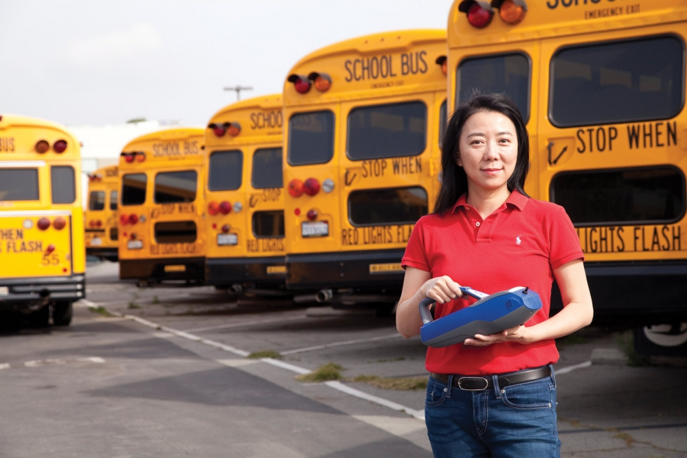 Yifang Zhu in front of buses