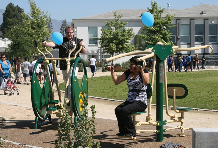 Adults using exercise equipment at a school playground as part of the federal Community Transformation Grant (CTG) in LA county.