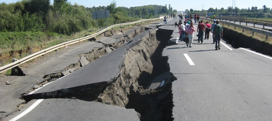 Earthquake-torn road with survivors walking in the distance