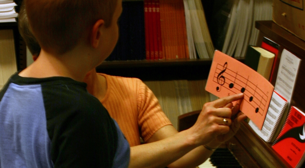 Boy learning how to read basic music notes from teacher at piano