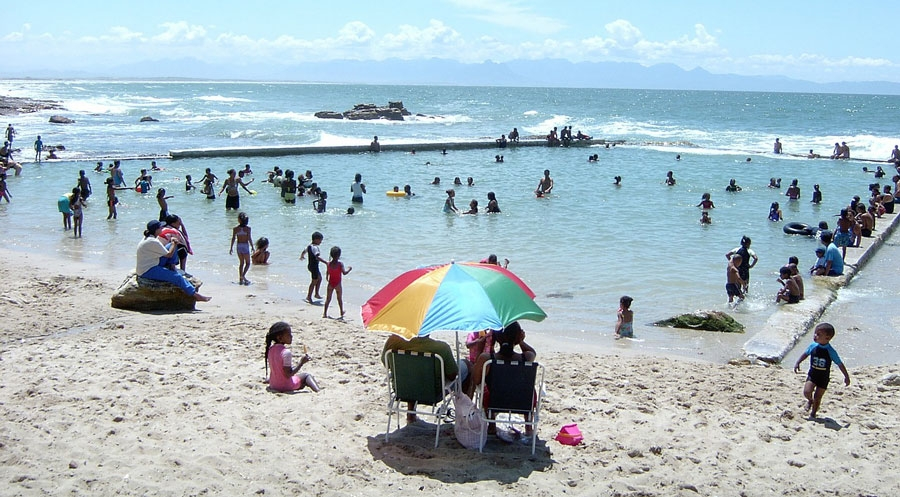 Families at a sunny beach with large umbrella