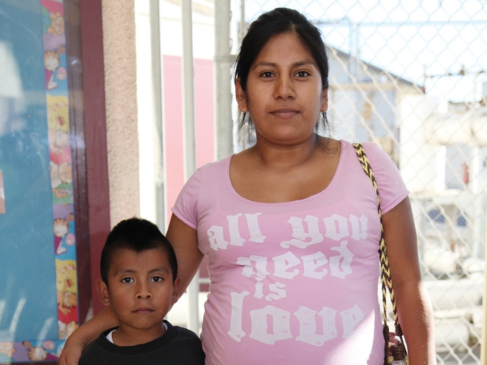 A Mixtec woman, who is pregnant and standing with her arm around her young son.