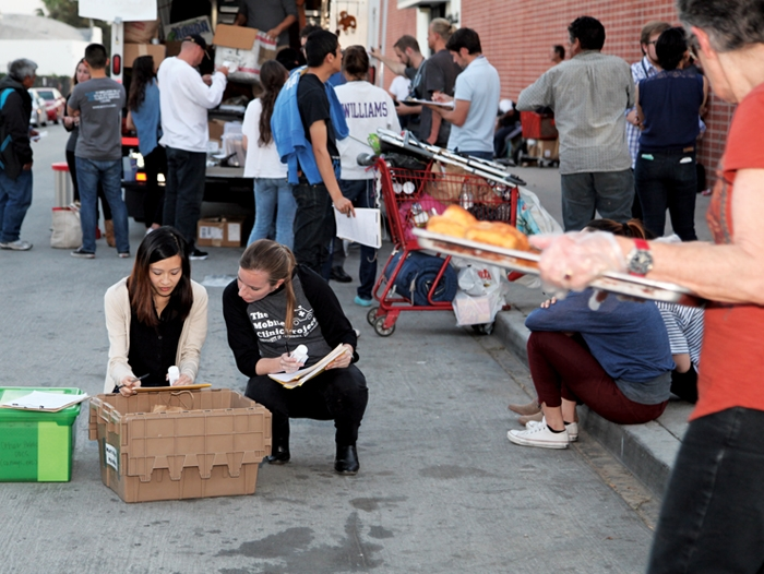 Two women checking on medical supplies from a box surrounded by people at the mobile clinic evening.