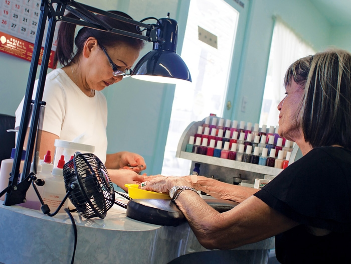 A manicurist and a customer in a nail salon.