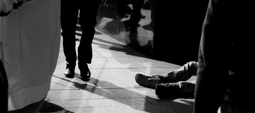 Black and white photo of homeless man's feet and other walking feet