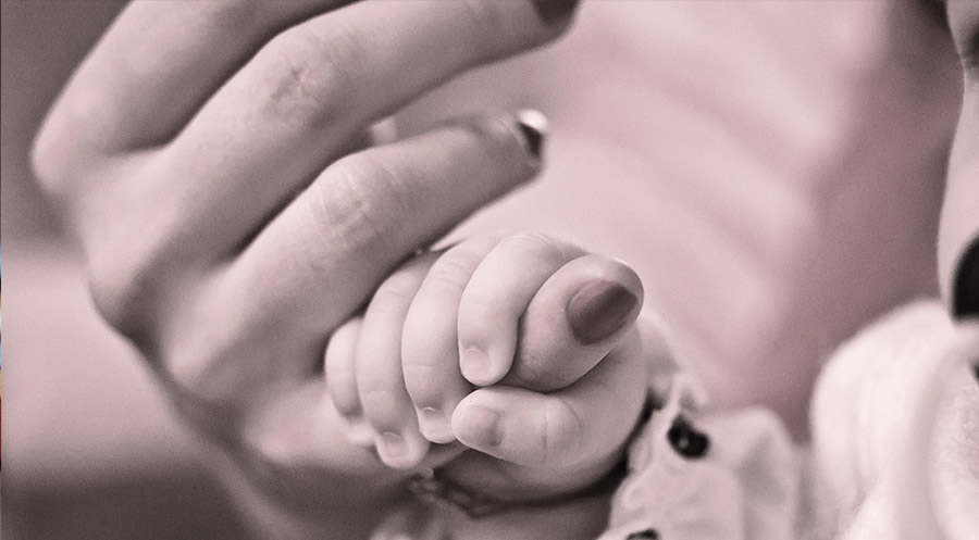 mother's hand hold an infant hand