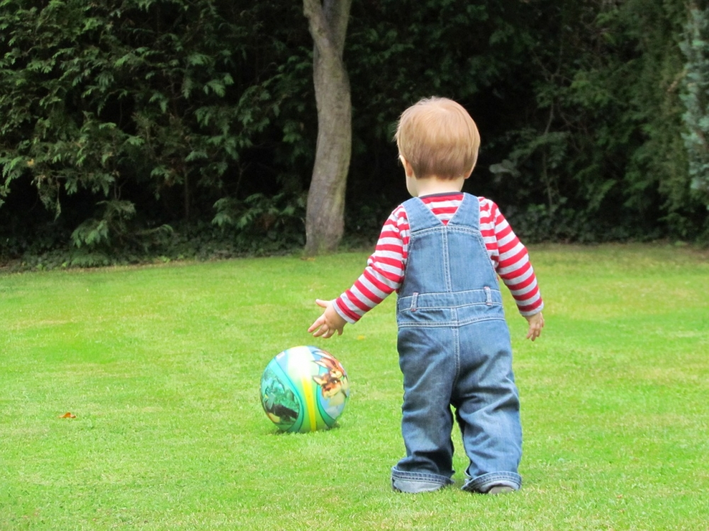 Child playing on green grass