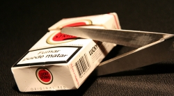 scissors cutting cigarette pack