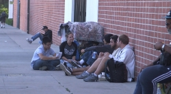 FSPH students sitting on the sidewalk speaking with homeless men