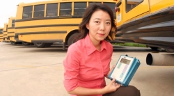 Yifang with equipment kneeling behind a school bus