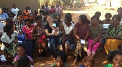 Claudia Gilmore surrounded by women and children in Zambia