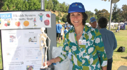 Thumbnail of Wendy Slusser with booth display at outdoor health fair
