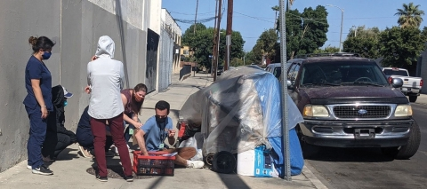 Anna Bratcher (leaning down, wearing purple), Housing for Health staff member Nicolas Leachman and colleagues provide vaccine education along with food, water, and clean needles to people experiencing homelessness, leading up to a pop-up vaccine clinic event in Reseda, California.