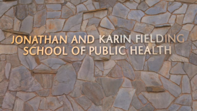 """Stone wall with gold words: """"Jonathan and Karin Fielding School of Public Health"""""""