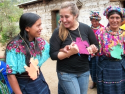 a female Peace Corps volunteer holding hands with local women