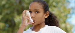 Girl using inhaler / iStockPhoto