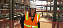 Krisianna Bock wearing hard hat and orange vest at construction site