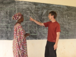 Philip Massey working at a chalkboard with a woman