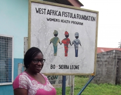 Dayo Spencer-Walters in Sierra Leone by a sign