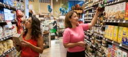 Two women looking at products in the aisle of a grocery store.