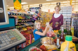 mother and daughter smiling in the checkout line buying groceries