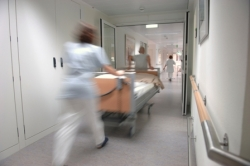 hospital staff moving a bed quickly down a hallway