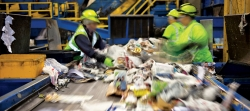 Three people working on the recycling line of waste management plant.