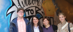 Artist Adam Talan, Dean Jody Heymann, Public Health Student Association co-presidents Harmony Larson and Kelsey Ferguson (l. to r.) stand in front of Adam's graffiti-style treatment to various public health messages now brightening up the tunnel entrance to the school while it's under renovation.