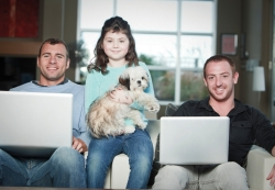 male couple sitting happily with daughter and puppy