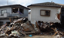 homes destroyed by a tsunami with debris all around