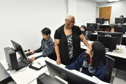 Dr. Lisa Smith speaking with students working at their computers.