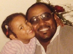An African-American man with his daughter smiling.