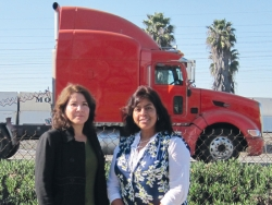 Two women standing in front of a large 18-wheeler truck.