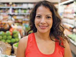 A young woman, Mirna Troncoso Sawyer, standing in a grocery store smiling.