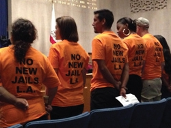 """a small group of protesters in court with orange t-shirts with the slogan """"no new jails LA"""""""