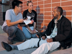 A young man and woman talk with an African-American homeless client.