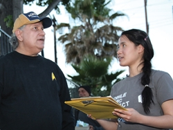 A young woman taking a survey from a man who is a homeless client.