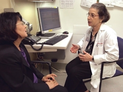 Dr. Patricia Ganz talking with associate in her office.