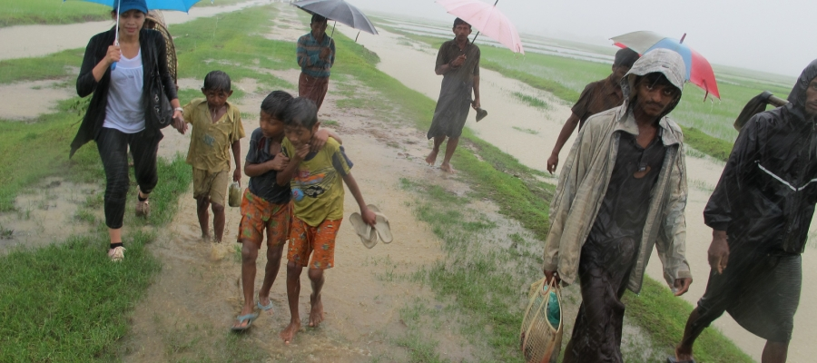 Dirna Mayasari walking in the rain with villagers