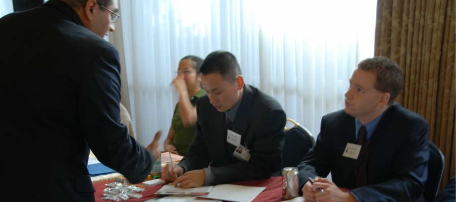 Two men  sitting behind a career fair table speaking with a student