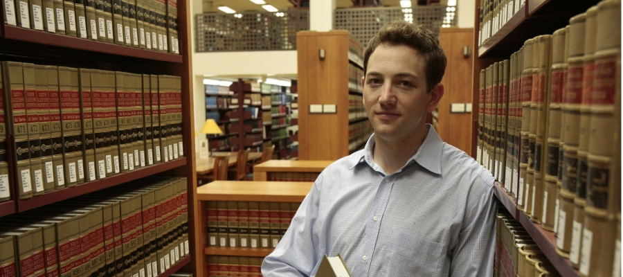 Eli Tomar holding a book in a law library