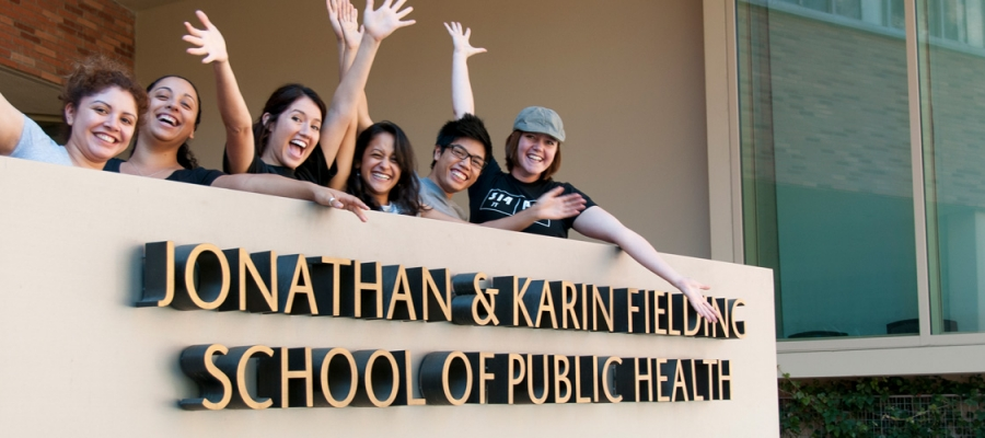 Students raising their arms and smiling behinf the main Fielding School sign