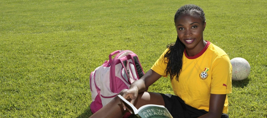 Mimi Nartey posing on a soccer field with gear and a book