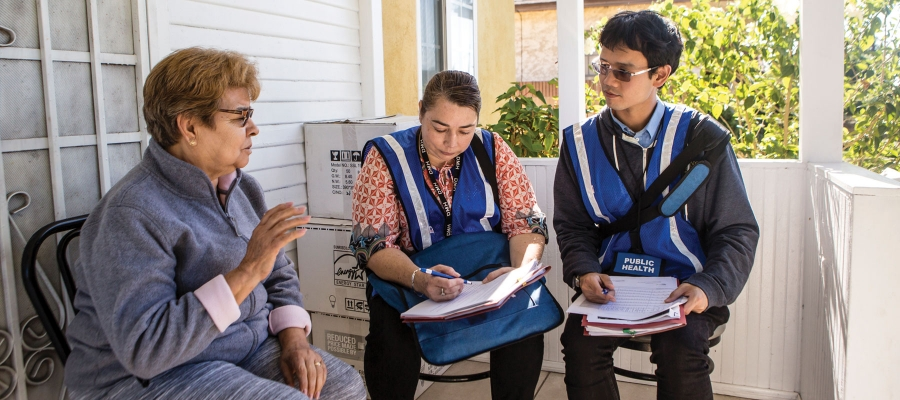 FSPH students sitting in the poch of a house with a promotora de salud
