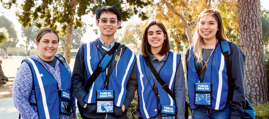 Students wearing blue  vests and public health badges