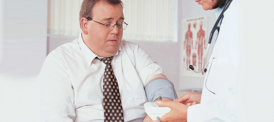overweight man having his blood pressure checked