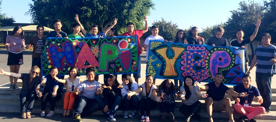 "A group of students with a large sign ""HAPI YEP"""