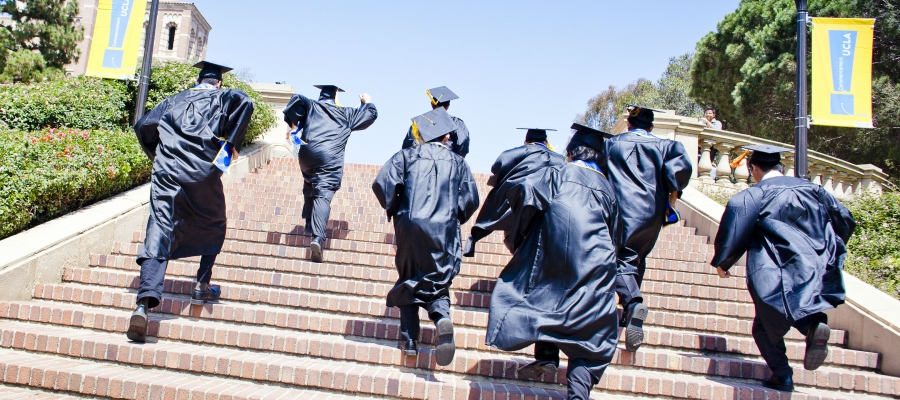 cap and gown students running up Janss steps