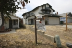 foreclosed houses with signs in their yards